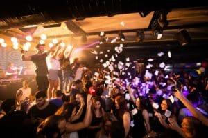 people on stage at a club on campus throwing paper into the crowd of dancing college students