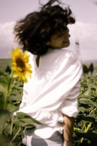 unfocused woman smiling over her shoulder in a sunflower field