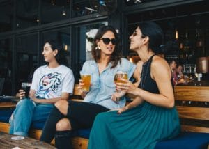 mom sits on restaurant bench chatting and drinking beers while daughter looks away