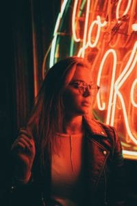 woman with glasses next to red neon sign