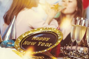 women in background drinking champagne with new year decorations and champagne on table
