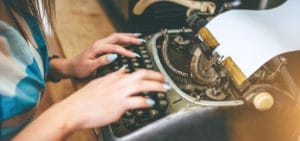 woman writes amends on old fashioned typewriter