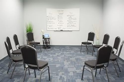 chairs circled in a meeting room with whiteboard