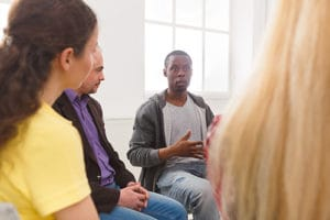 Man speaking in therapy at his drug addiction rehab center