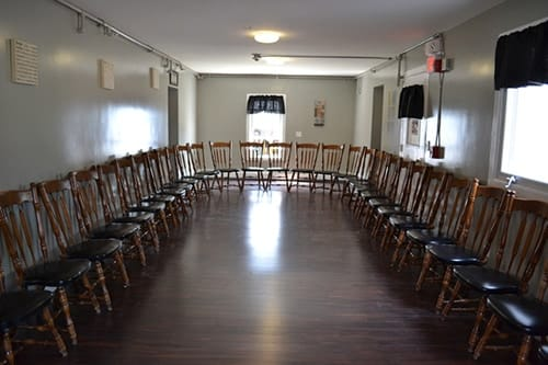 long room with chairs lined along walls at mens rehab center