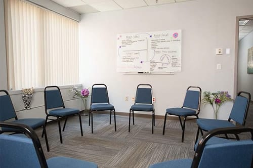 chairs in a circle with whiteboard at granite house for women