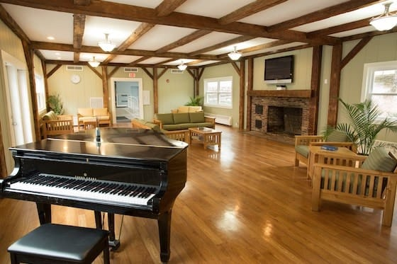 piano, seats, fireplace, tv of green mountain treatment center common area