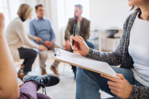 counselor in group therapy with clipboard talks to single patient about crystal meth vs meth while other patients talk in background