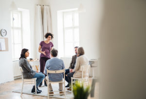 counselor talks to circle of patients in a living room talking about sober houses in mass