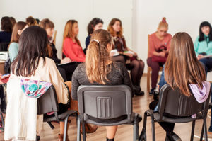 a large group of women sit and talk at a womens rehab center