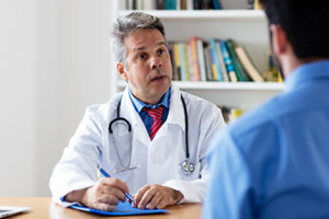 concerned doctor talks to male patient in a codeine detox center