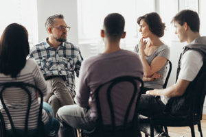 group of people sitting in a circle in alcohol rehab center program in Boston MA