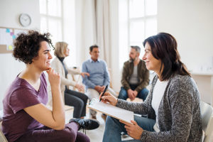 drug rehab program Portsmouth NH, therapist talking with woman in group
