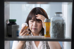 myths about drugs, woman looking through medicine cabinet confused