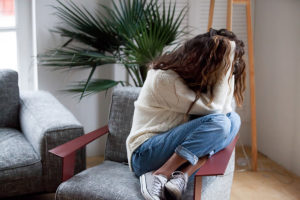 physical dependence, woman curled up on chair