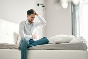 suboxone withdrawal symptoms, man sitting on bed holding himself in pain