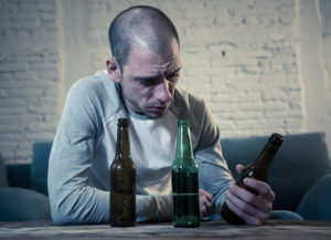 symptoms of addiction, man staring forlorn at beer bottles