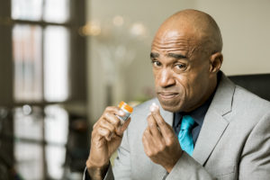 what is fentanyl, man about to take a pill with a strange look on his face